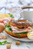 Бейгл с салатом arugula, огурца и бекона для завтрака Стоковая Фотография