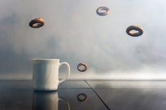 Бейгл с маковыми семененами летают над чашкой кофе Стоковое фото RF