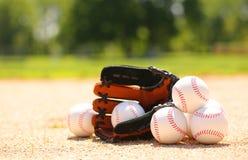 Бейсболы и перчатка на поле стоковое изображение rf