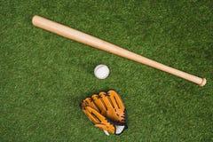 Бейсбольная бита с перчаткой и шарик на зеленой траве Стоковое Фото