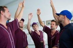 Бейсбольная команда делая максимум 5 с тренером стоковое фото rf