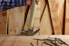 Бейте молотком для того чтобы извлечь ноготь загиба на древесине стоковое изображение rf