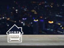 Бейте молотком и взламывайте с значком дома на деревянном столе над colo нерезкости Стоковое Изображение RF