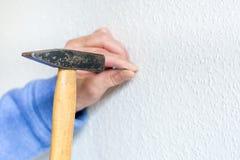 Бейте ноготь молотком в белую стену стоковое изображение rf