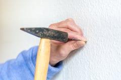 Бейте ноготь молотком в белую стену стоковые изображения