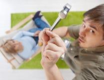 бейте ноготь молотком человека удерживания Стоковое Изображение