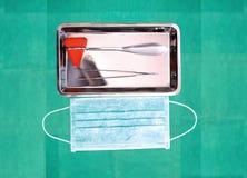 Бейте рывок с пинцетом в подносе и маску молотком рядом с на dres хирургии Стоковое Фото