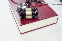 Бейте судьи, стетоскопа и книги молотком на белой предпосылке Стоковые Фото
