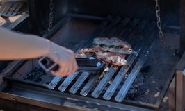 Бекон варя на барбекю угля с руками держа пару схватов стоковое изображение rf