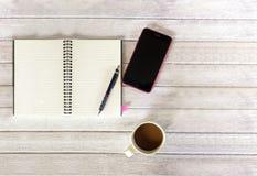 Белая бумага и Smartphone на деревянной таблице Стоковое фото RF