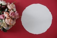 Белая бумага модель-макета с космосом для текста или изображение на красных предпосылке и цветке стоковое фото rf