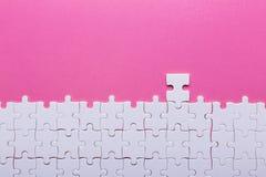Белая головоломка на розовой предпосылке Взгляд сверху стоковая фотография