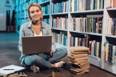 Белая девушка около книжных полок в библиотеке Студент использует компьтер-книжку стоковая фотография