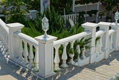 Белая декоративная загородка с фонариком на шагах и в зеленой вегетации стоковая фотография