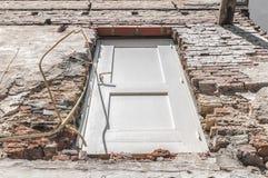 Белая деревянная дверь видимая в каменной стене стоковые фото
