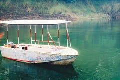 Белая деревянная шлюпка на речном береге, окруженном лесами мангровы Круиз джунглей перепада реки Рыболов и туристские весельные  стоковое фото rf