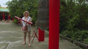 Белая женщина поражает колокол на буддийском виске в Таиланде сток-видео