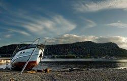 Белая и красная шлюпка силы на скалистом береге озера горы с зданиями и леса на далеком банке с голубым небом и белизной Стоковая Фотография