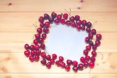 Белая карточка для примечаний с вишнями на деревянной предпосылке Стоковая Фотография RF