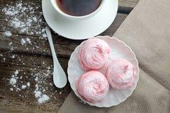 Белая керамическая чашка с десертом черного кофе и зефира на деревянном столе, взгляд сверху Стоковые Фото