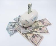 Белая копилка на куче валюты Соединенных Штатов против белой предпосылки стоковое фото