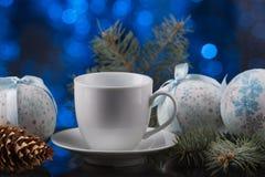 Белая кофейная чашка в праздничном украшении, рождестве забавляется, голубая предпосылка bokeh Стоковая Фотография