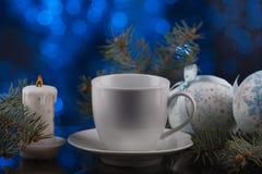 Белая кофейная чашка в праздничном украшении, рождестве забавляется, голубая предпосылка bokeh Стоковое Изображение