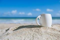 Белая кофейная чашка эспрессо с океаном, пляжем и seascape стоковые изображения