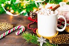 Белая кружка какао с зефирами, леденцами на палочке, конусами ели, ветвью рождественской елки, гирляндой и снежинкой на деревянно стоковое фото