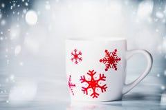 Белая кружка с красными снежинками на голубых снежностях предпосылке, вид спереди Счастливая карточка зимнего отдыха Стоковые Изображения RF