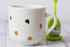 Белая кружка с infuser сердца и чая Стоковые Изображения