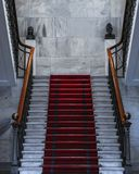 Белая лестница с красным ковром на верхней части стоковое фото