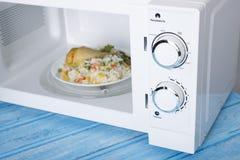 Белая микроволновая печь, на голубой деревянной поверхности для нагревая еды Стоковое Изображение