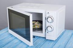 Белая микроволновая печь, на голубой деревянной поверхности для нагревая еды Стоковая Фотография RF