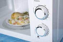 Белая микроволновая печь, на голубой деревянной поверхности для нагревая еды Стоковые Фото