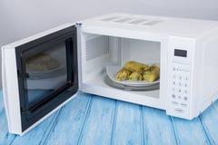 Белая микроволновая печь, на голубой деревянной поверхности для нагревая еды Стоковая Фотография