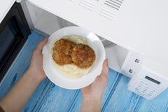 Белая микроволновая печь, на голубой деревянной поверхности для нагревая еды Стоковое Изображение RF