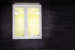 белая оконная рама, желтый свет внутри окна, на черной кирпичной стене стоковые изображения