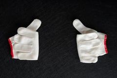Белая перчатка с жестом больших пальцев руки вверх дальше подпирает стоковые фото