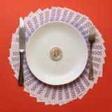 Белая плита с столовым прибором и bitcoin монетки на скатерти сделана счетов евро на красной предпосылке стоковое фото