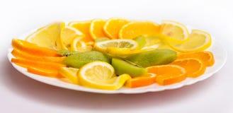Белая плита с tangerines, апельсинами и кивиом на праздничной таблице стоковая фотография