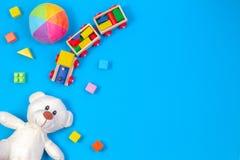Предпосылка игрушек детей младенца Белая плюшевый мишка, деревянный поезд, красочные блоки на голубой предпосылке стоковое изображение