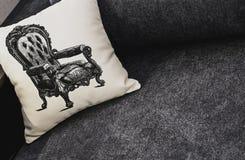 Белая подушка с картиной на серой софе Остатки, спать, концепция комфорта Белая подушка с картиной кресла стоковые фотографии rf