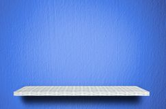 Белая полка на голубой предпосылке цемента для дисплея продукта стоковое изображение rf