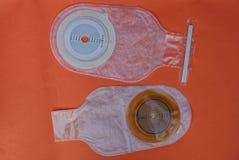 Белая пустая медицинская сумка colostomy 2 на красной таблице стоковое фото rf