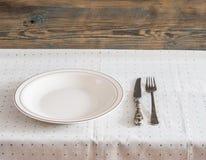 Белая пустая плита с вилкой и нож на скатерти точки польки Стоковая Фотография RF