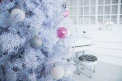 Белая рождественская елка украшенная с серебряными и розовыми орнаментами на предпосылке рояля alps покрыли древесины зимы малого стоковая фотография