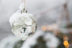 Белая серебряная безделушка орнамента рождества Beautyful haning на ели с снегом Стоковая Фотография