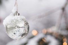 Белая серебряная безделушка орнамента рождества Beautyful haning на ели с снегом Стоковая Фотография RF