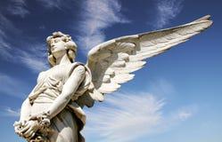 Белая скульптура мрамора ангела с открытыми длинными крылами на ярком солнечном голубом небе Стоковое фото RF
